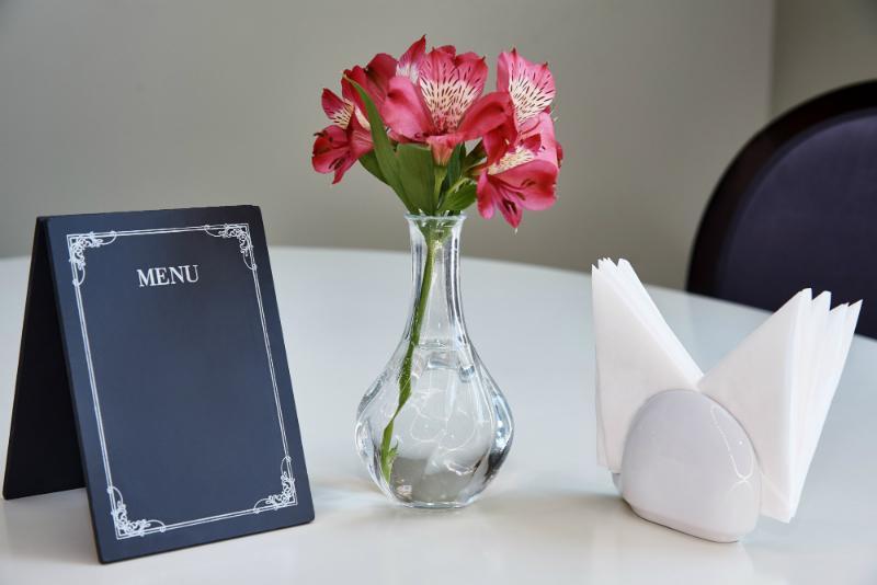Lilien in Glasvase als stilvolle Tischdeko zum Dinner