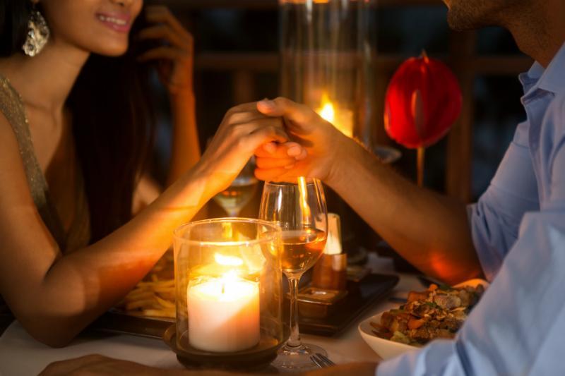 Romantisches Paar haelt Haendchen beim Dinner