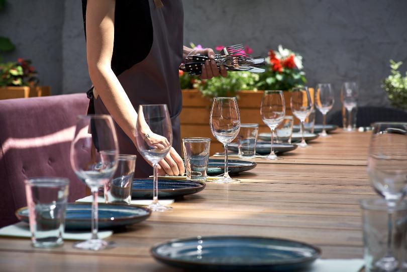 Frau deckt dekorativen Tisch im Garen ein - Tisch richtig decken