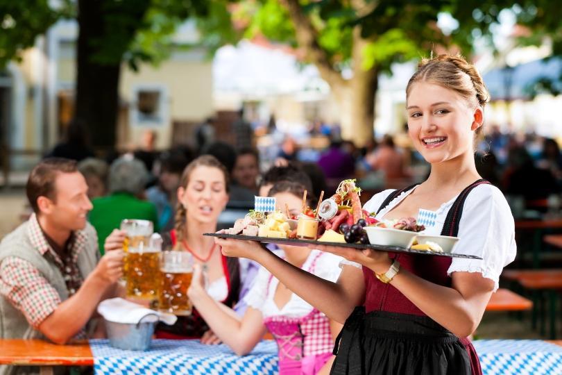 Junge Kellnerin im Biergarten - bayrisches Frühstück