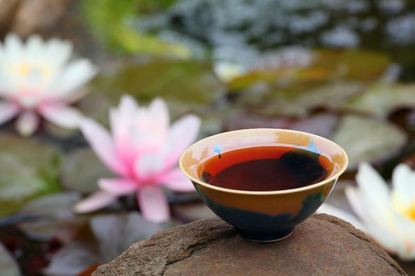 Schale mit Tee vor einem Hintergrund mit Seerosen