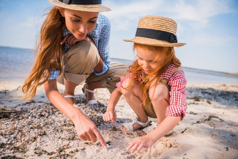 Mutter mit Tochter sammelt Muscheln
