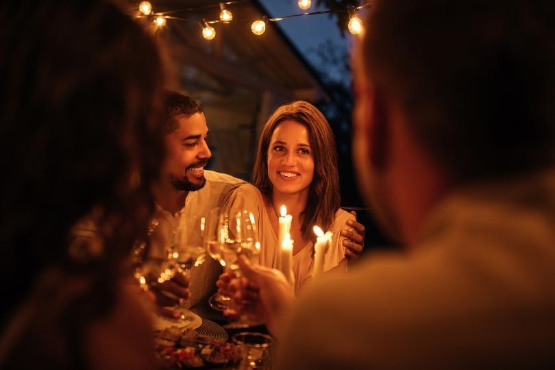 Junges paar stösst mit Freunden an - Hochzeitstag feiern in Zeiten von Einschränkungen