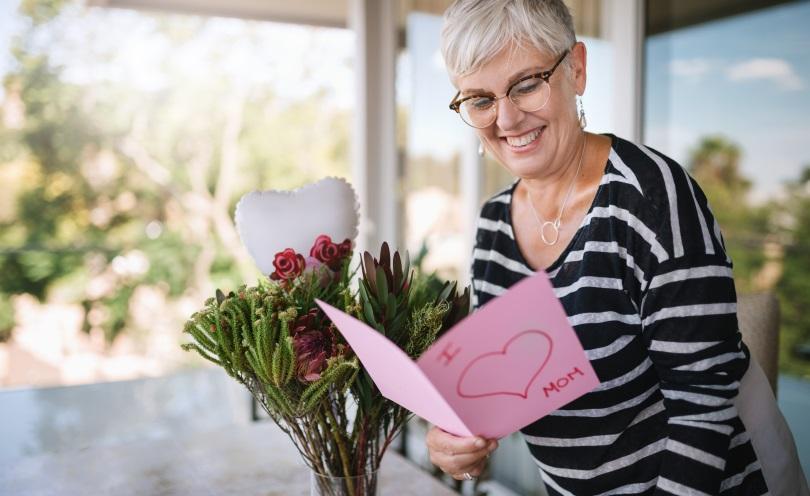 Eine ältere Mutter freut sich über eine Karte und einen Blumentrauß Geschenke zum Muttertag