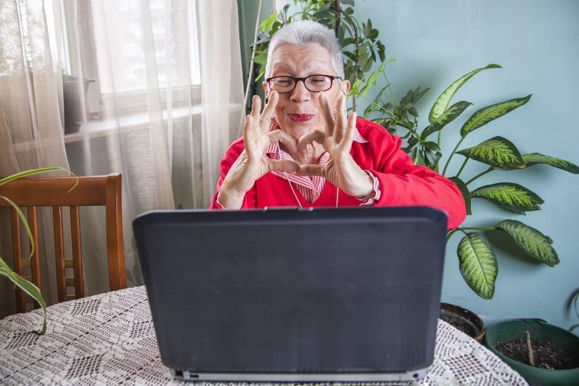 Eine ältere Frau formt Daumen und Zeigefinger zu einem Herz, während Sie über den Laptop mit Ihren Lieben kommuniziert Geschenke zum Muttertag