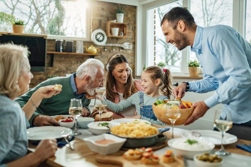 Familie mit Großeltern beim Essen - zum Beispiel bei einer Einschulungsfeier