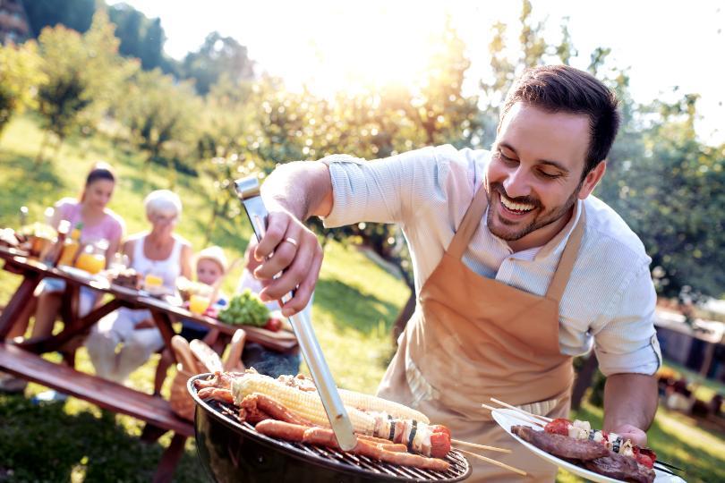 Mann grillt für seine Familie im Hintergrund - Grillfeier organisieren