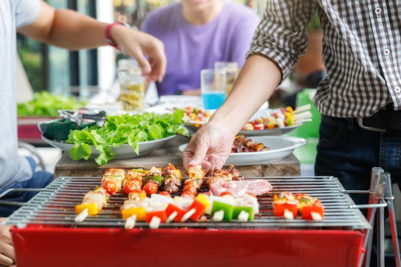 Im Vordergrund ein Mann am Grill, im Hintergrund ein paar essende Menschen - Grillfeier organisieren