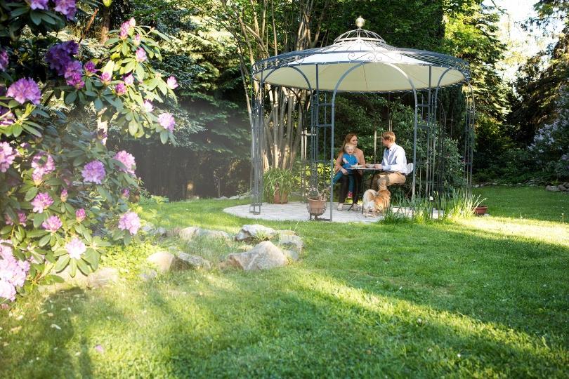 Eltern mit Kind sitzen im Gartenpavillon
