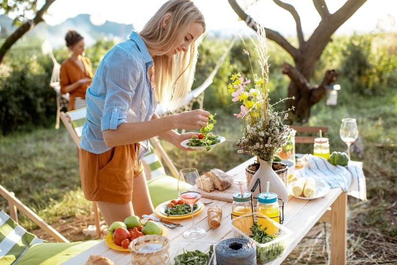 Junge Frau an einem dekorierten Party-Tisch im Garten - Trotz Corona mit Freunden feiern