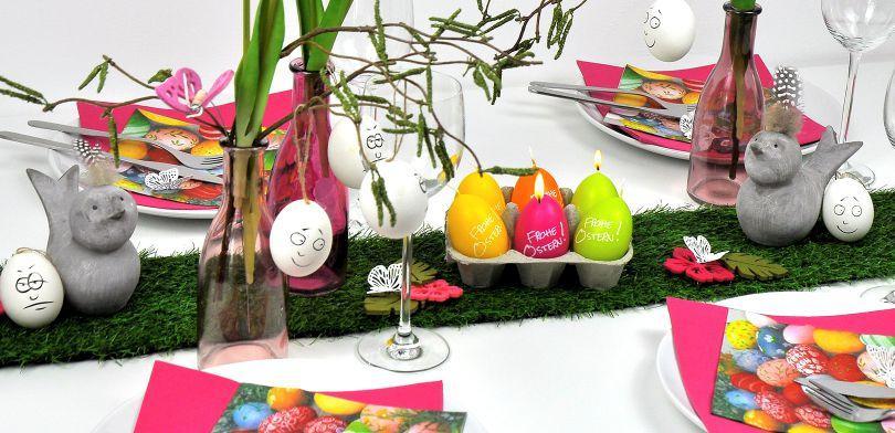 Pfiffiger Ostertisch mit Grastischband, lustigen Eiern und Ostereierkerzen im Eierkarton
