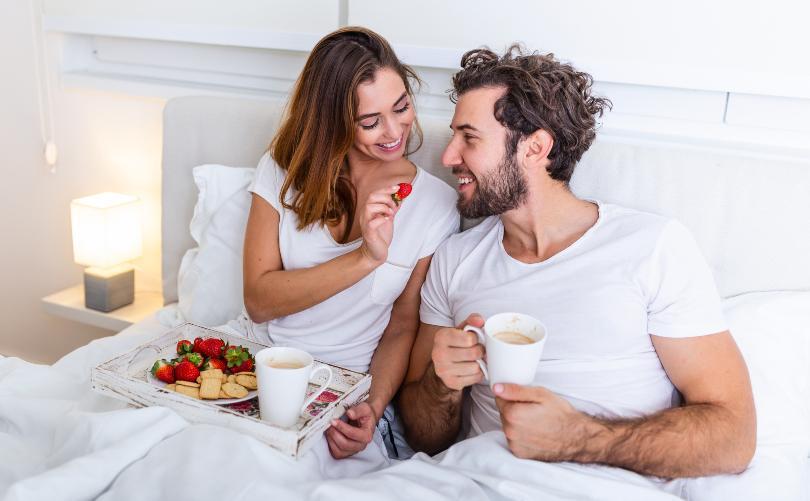 Junges Paar frühstückt im Bett - Romantischer Tag zu zweit