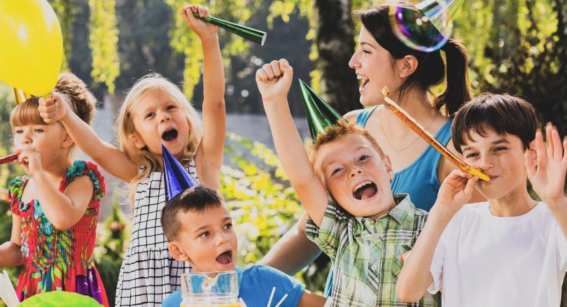 Kinder feiern zusammen mit einer Mutter einen fröhlichen Kindergeburtstag