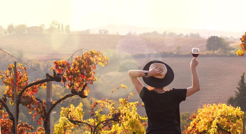 Frau mit Weinglas steht im Herbst an einem Weinberg - Erntedank-Zeit