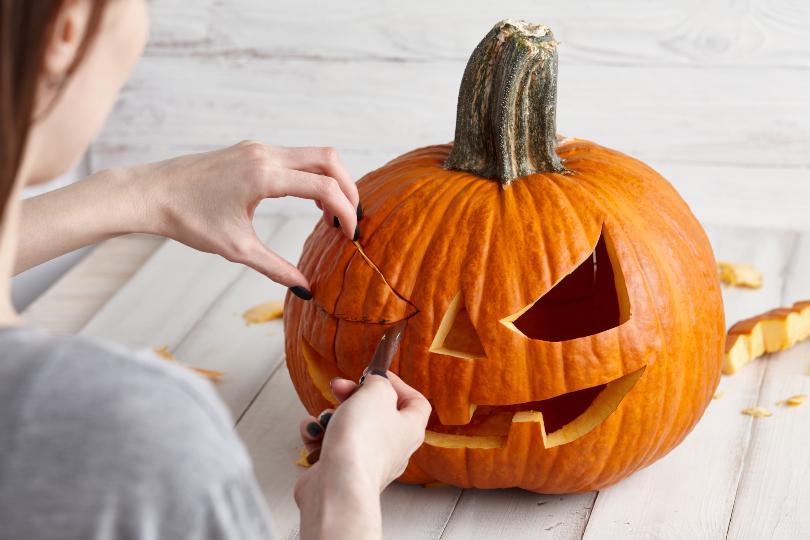 Frau schneidet Kürbis für Halloween
