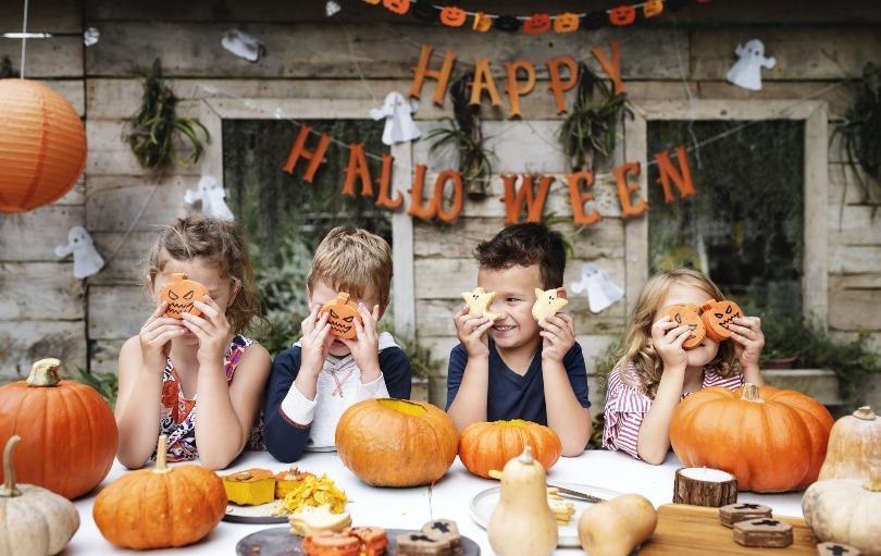 Kinder sitzen am Halloween-Tisch