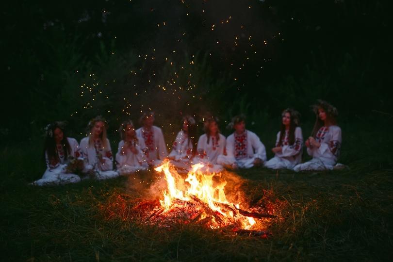 Gruppe junger Frauen in Trachten sitzt um Lagerfeuer