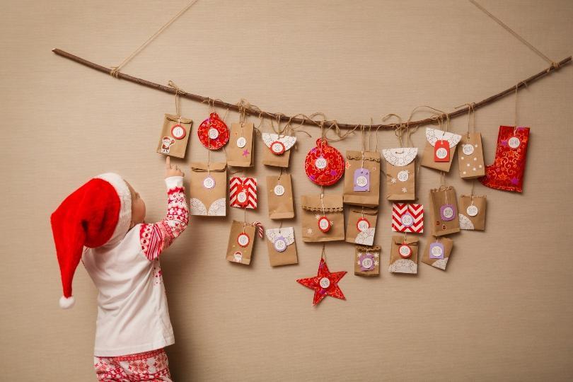 Kind greift nach Täschchen einen Adventskalenders - Geschenke zu Weihnachten