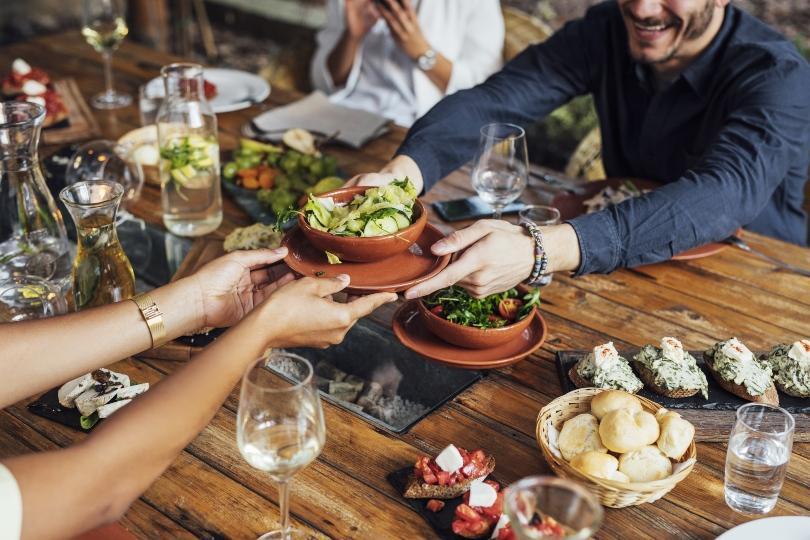 Mann reicht Frau am Esstisch einen Salat - Dinner mit Freunden