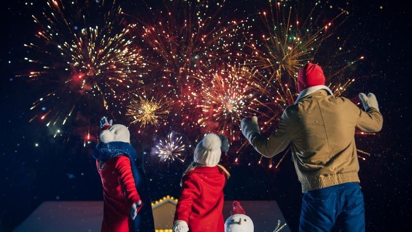 Vater mit weit Kindern beobachten großes Feuerwerk - Kleine Feier zu Silvester