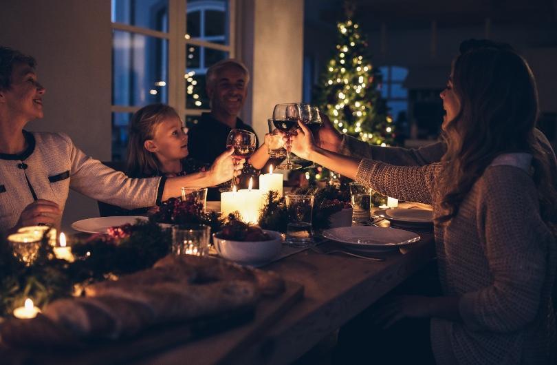 Familie feiert Weihnachten zusammen am Esstisch - Stimmungsvolle Wintertischdeko
