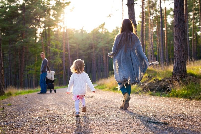Junge Familie spaziert im Wald