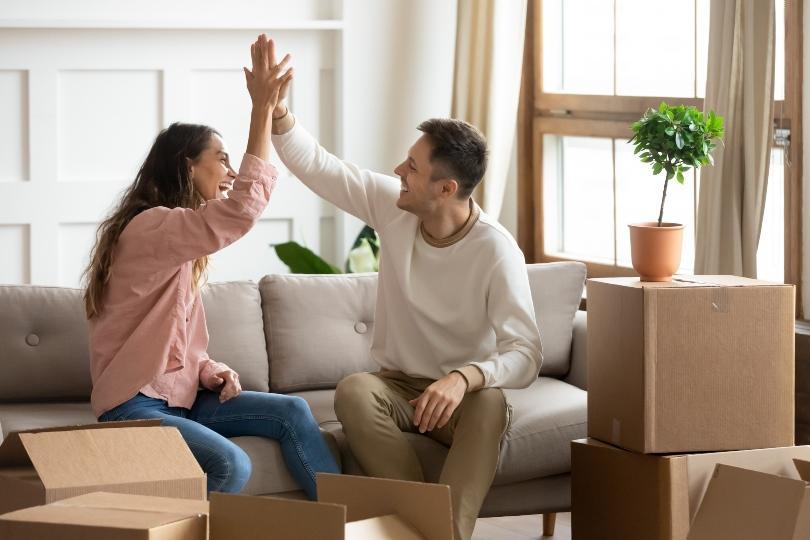 Junges Paar beglückwünscht sich zum Einzug - Einweihungsfeier in kleinem Kreis