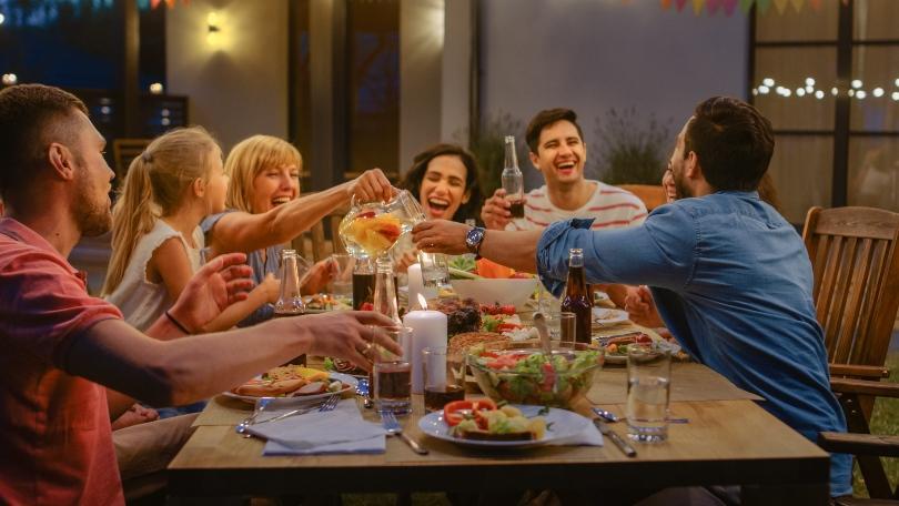 Freunde/Familie feiern gemeinsam am gedeckten Tisch - Wiedersehen nach langer Zeit