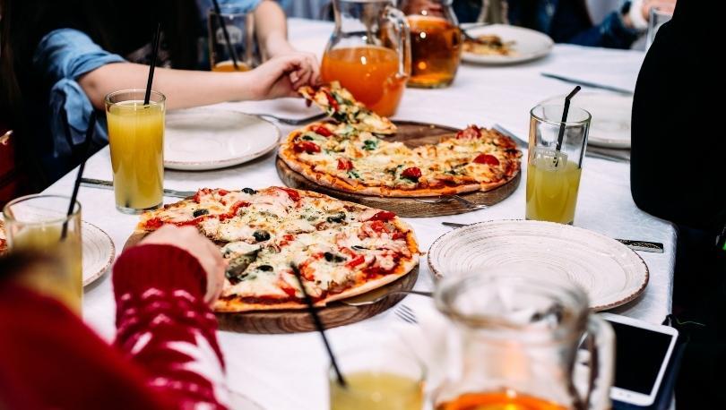 Leute essen Pizza am Tisch