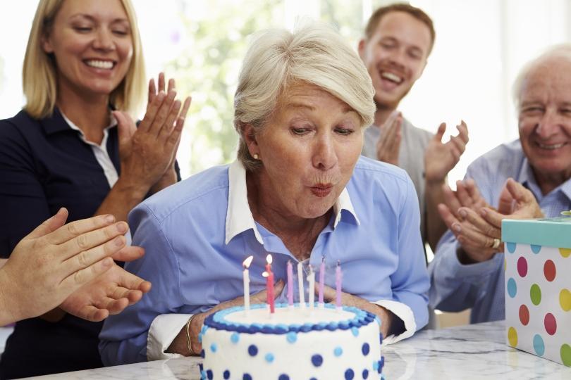 Seniorin bläst Geburtstagstorte aus - Geburtstag mit Familie feiern