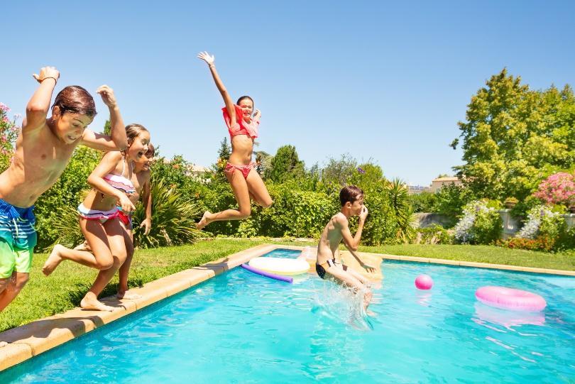 Kinder springen in einen Swimming Pool - Tischdeko zur Poolparty