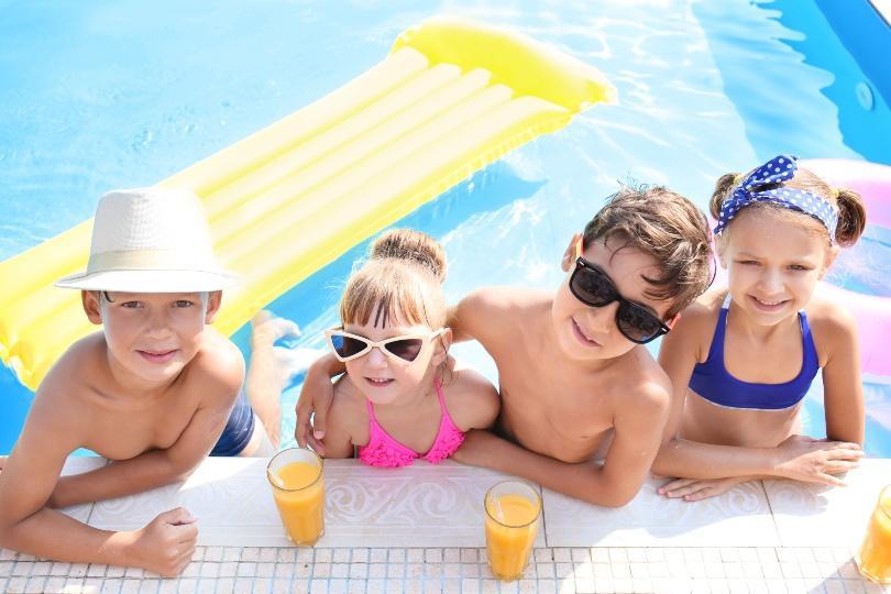 4 Kinder am Beckenrand mit Getränken