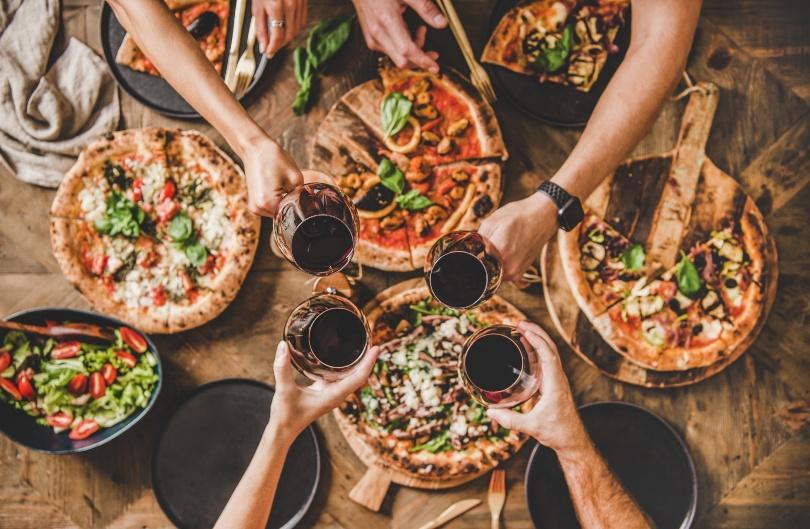 Foto von oben - Tisch mit Pizzen und Leuten, die mit Wein anstoßen - Südländische Deko