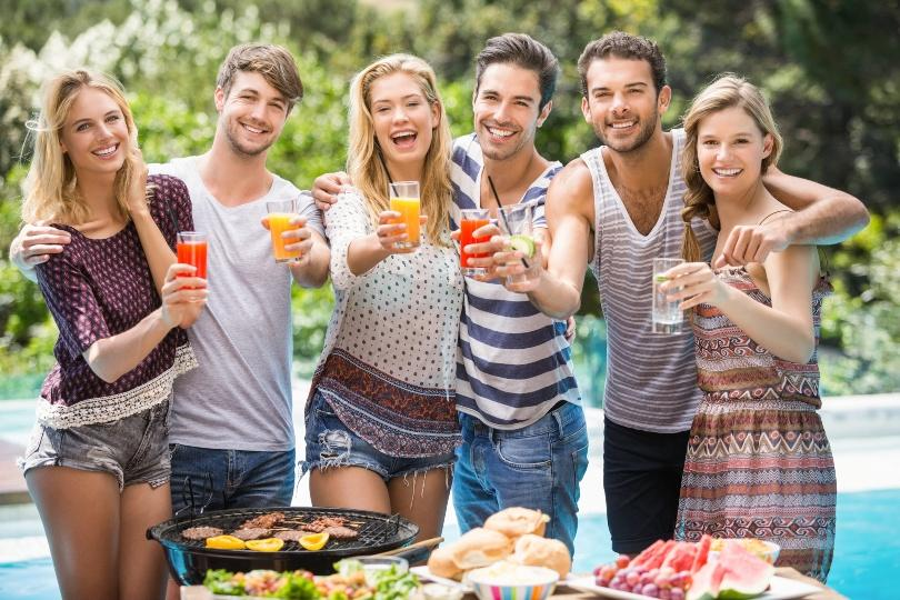 Junge Leute mit Drinks vor einem Swimming Pool