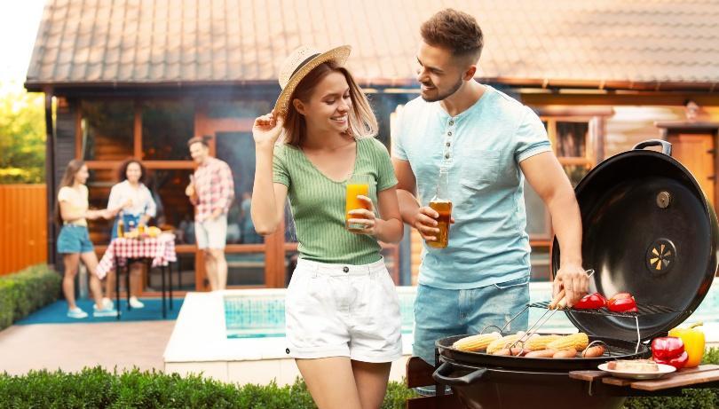 Junges Paar am Grill, im Hintergrund weitere Gäste am Swimming Pool - Tischdeko zur Poolparty