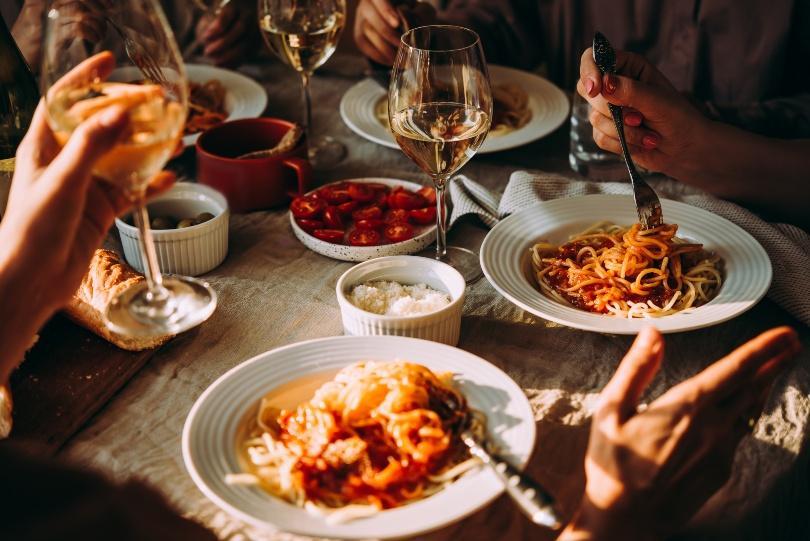 Leute sitzen am Tisch und essen Pasta und trinken Wein