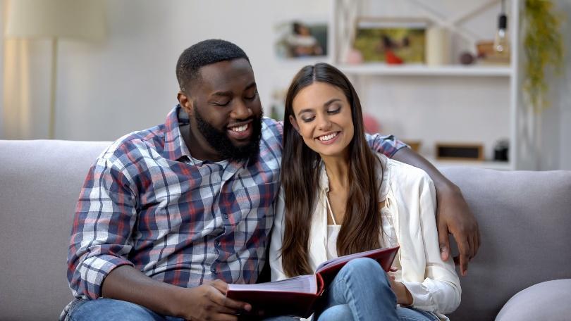 Junges Paar schaut gemeinsam Fotos an