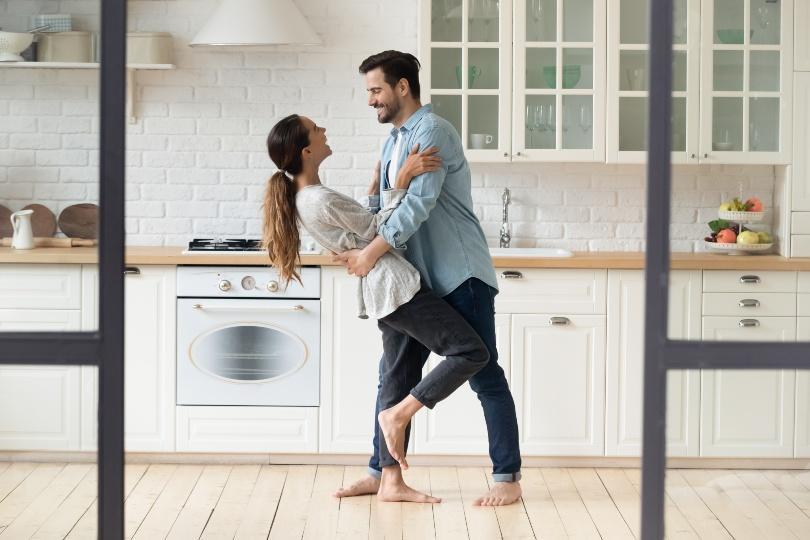 Junges Paar tanzt in der Küche - die Papierhochzeit ist das erste Hochzeitsjubiläum