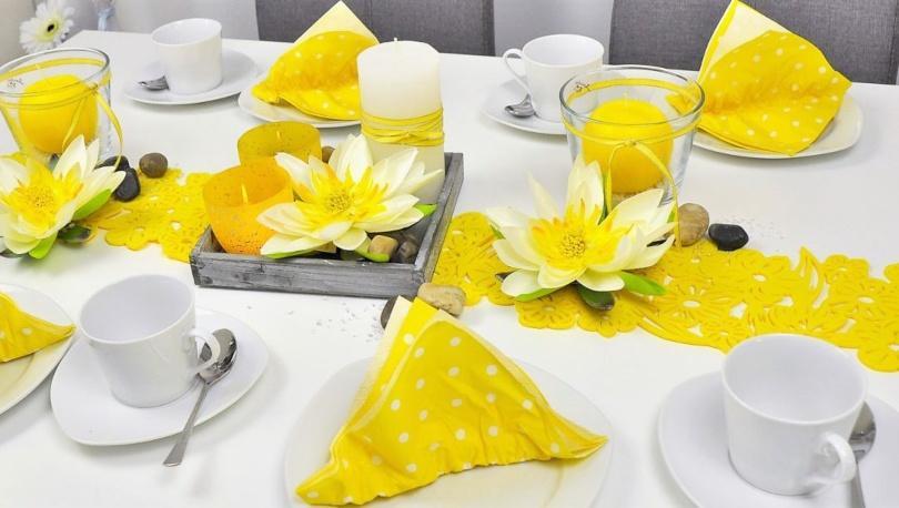 Sommerliche Tischdekoration in Gelb mit Lotusblüten
