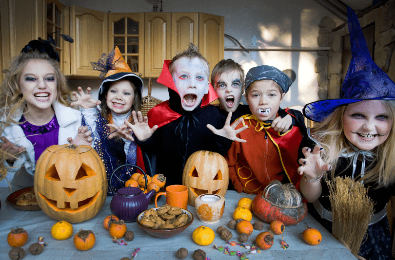 Kinder feiern Halloween in Kostümen - Halloweendeko