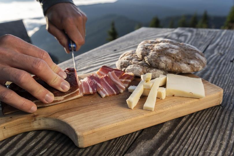 Jemand schneidet Schinken - traditionelle Jause/Brotzeit in den Bergen