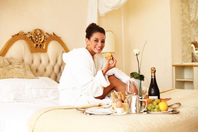 Junge Frau im Bett mit Frühstück